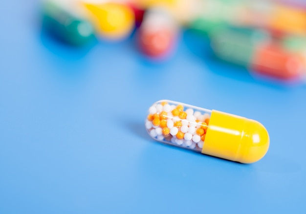 Capsule jaune avec un médicament sur bleu