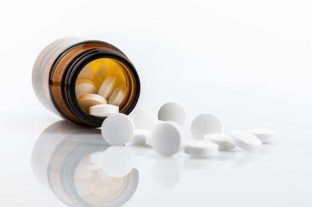 Capsule de médecine renversée en bouteille isolé sur fond blanc