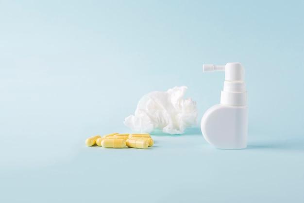 Capsule, médicaments, lingettes en papier froissé et spray pour l'écoulement nasal et la gorge sur fond bleu. maladies saisonnières et traitement du rhume, de la grippe, de la chaleur. prévention des virus