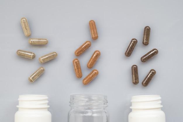 Capsule médicinale déversée de trois bouteilles en plastique sur une surface claire