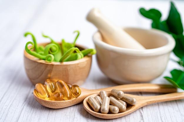 Capsule organique à base de plantes de médecine alternative avec de la vitamine e, huile de poisson oméga 3, minérale, médicament avec feuille d'herbes.