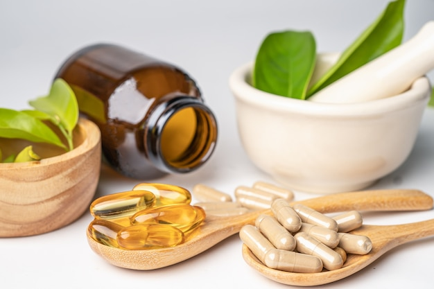 Capsule organique à base de plantes de médecine alternative avec de la vitamine e oméga 3, huile de poisson, minérale, médicament avec des suppléments naturels de feuilles d'herbes pour une bonne vie saine.