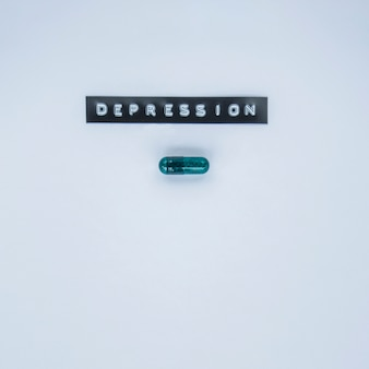 Capsule verte avec étiquette de dépression sur fond gris