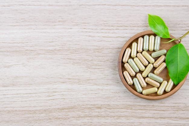 Capsule de vitamine dans la médecine à base de plantes bio de disque en bois de la nature