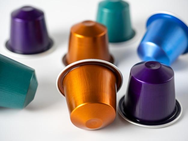Capsules en aluminium colorées avec du café moulu sur fond blanc. capsules pour la machine à café
