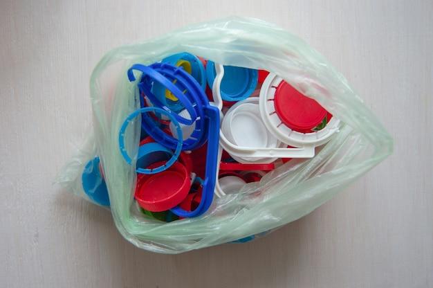 Capsules de bouteilles dans un sac en plastique un fond blanc