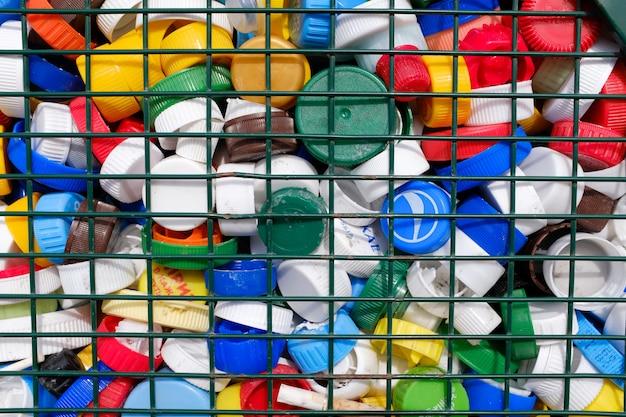 Capsules de bouteilles en plastique colorées derrière des barres de fer. concept: gestion des déchets, protection de l'environnement, collecte séparée des déchets. déchets plastiques.
