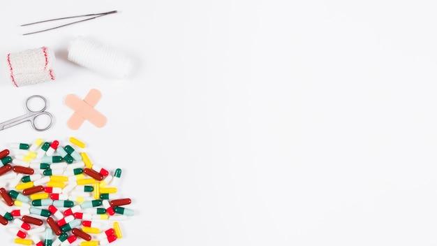 Capsules colorées et équipements médicaux isolés sur fond blanc