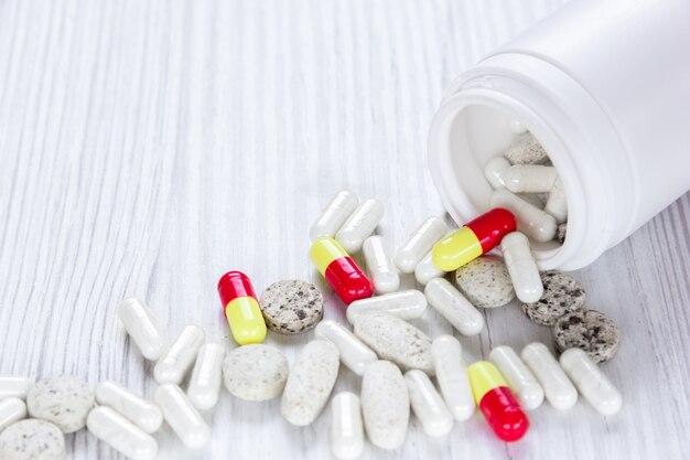 Des capsules colorées de pilules sortent de la bouteille