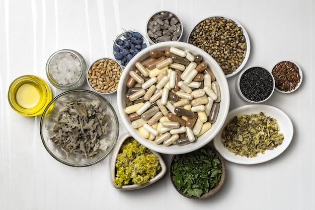 Capsules avec compléments alimentaires et ingrédients pour compléments alimentaires, minéraux, huiles et herbes en assiettes