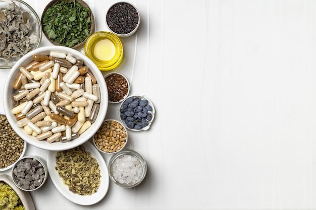 Capsules avec compléments alimentaires. ingrédients pour compléments alimentaires, minéraux, huiles et herbes en assiettes