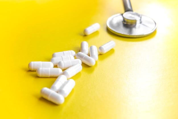 Capsules cylindriques blanches sur fond bleu mat dans un tube blanc. vue d'en-haut. concept médical de traitement, de prévention et d'effets secondaires.