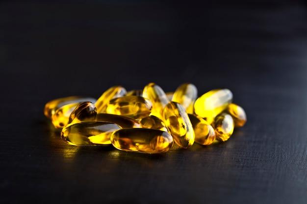 Capsules d'huile oméga-3 et vitamine pour les soins de santé sur tableau noir.