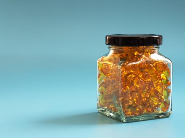 Capsules d'huile de poisson dans des bouteilles en verre sur fond bleu. oméga-3 et stéthoscope sains.