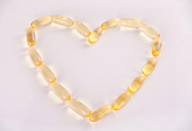Capsules d'huile de poisson en forme de coeur oméga 3 ou vitamine e. vitamines pour la promotion de la santé.