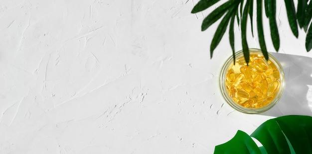 Capsules d'huile de poisson avec oméga 3 et vitamine d dans un bocal en verre sur une surface en béton blanc