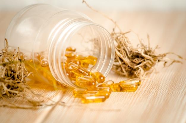 Des capsules d'huile de poisson se sont répandues dans un récipient ouvert.
