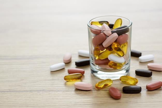 Capsules d'huile de poisson et suppléments de multivitamines dans le petit verre de la table en bois avec espace de copie.