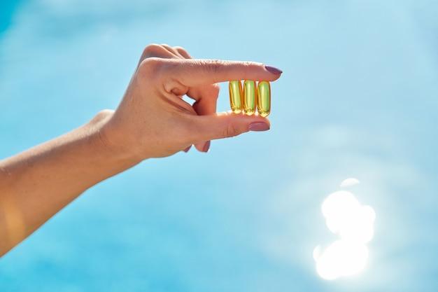 Capsules d'huile de vitamine d d'or ensoleillé omega-3 dans la main de la femme