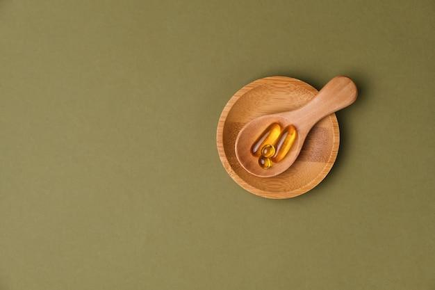 Capsules jaunes dans la cuillère en bois sur une surface verte