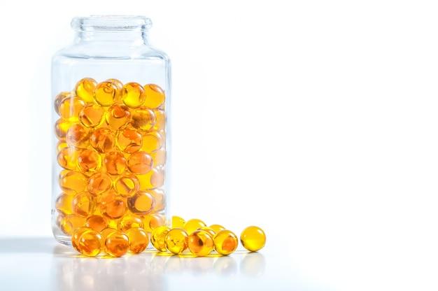 Capsules jaunes dispersées d'un bocal en verre sur un fond blanc.