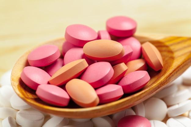 Capsules de médecine, pilules sur une cuillère en bois