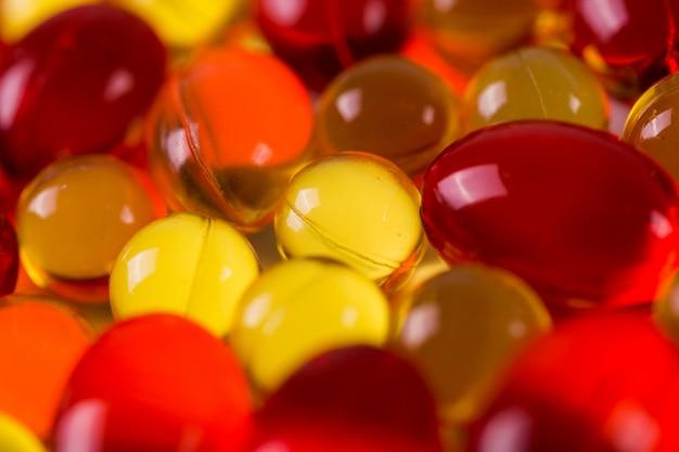 Capsules médicales jaunes et rouges sur une surface de miroir