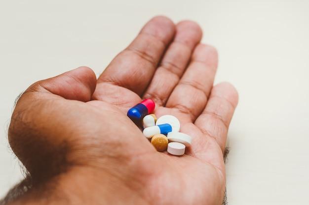 Capsules de médicaments (pilules assorties) dans la main d'un homme. fond clair. concept d'automédication, santé, dépression, cancer, médicaments.