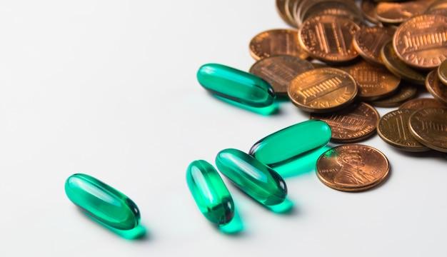 Capsules de médicaments transparents verts et pièces de 1 cent sur fond blanc