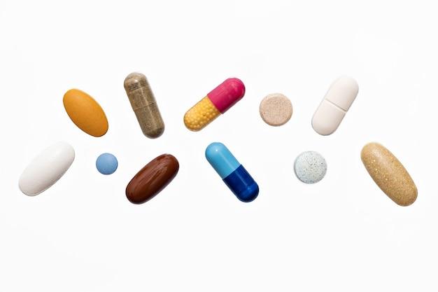 Capsules molles de poudre colorée pilule suppléments vitaminiques sur une surface blanche