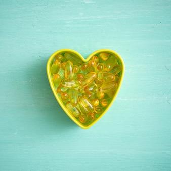 Les capsules d'oméga3 sont versées en forme de cœur sur un fond turquoise