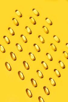 Capsules ovales jaunes capsules de vitamine oméga 3 modèle sans couture sur jaune