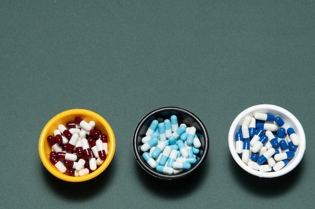 Capsules de pilule de médecine pharmaceutique, dans un bol en plastique sur mur gris