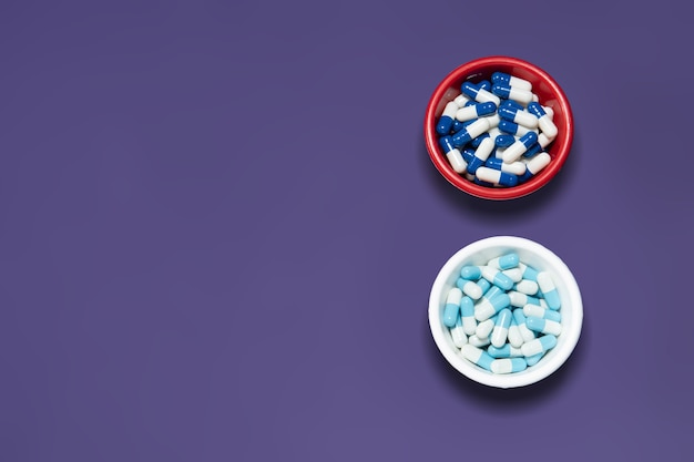 Capsules de pilule de médecine pharmaceutique, dans un bol en plastique sur un mur violet.