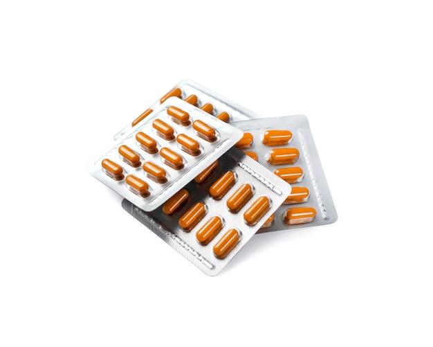 Capsules de pilule orange dans des blisters isolés sur une surface blanche