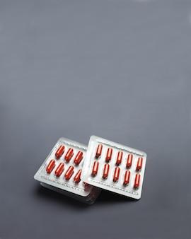 Capsules de pilule rouge sous blister sur une surface grise