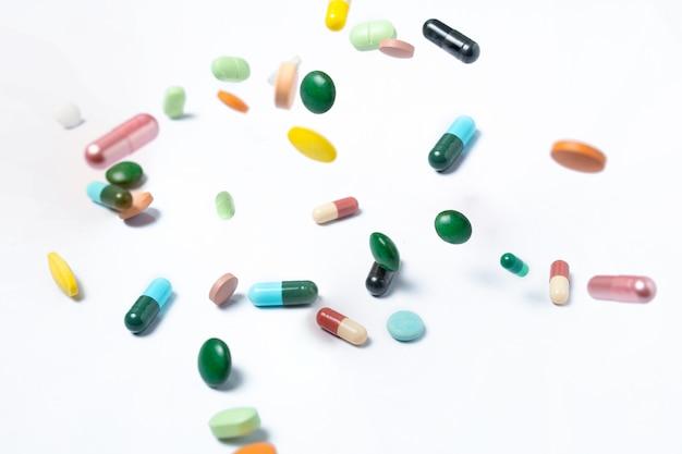 Capsules et pilules colorées sur blanc. santé
