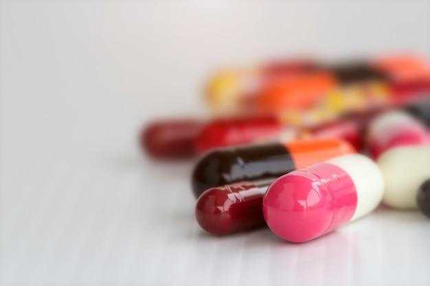 Capsules de pilules colorées sur blanc