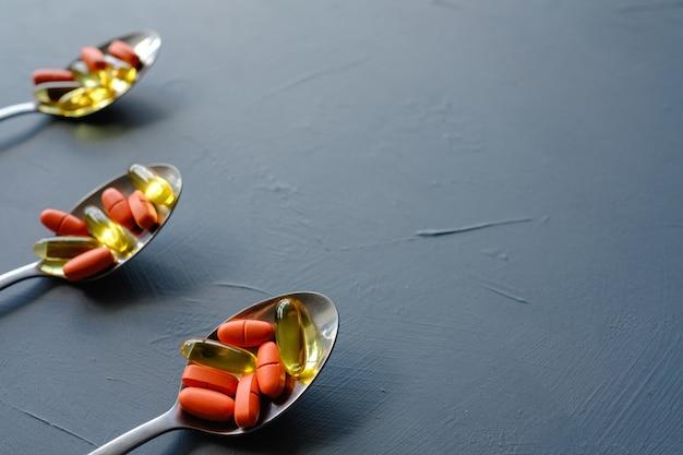 Capsules de pilules dans des cuillères. traitement médicamenteux et maladie
