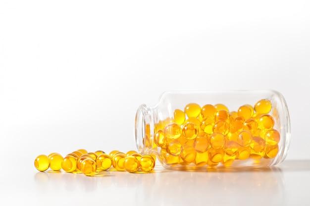 Capsules de pilules jaunes crumble d'une bouteille de verre sur un fond blanc.