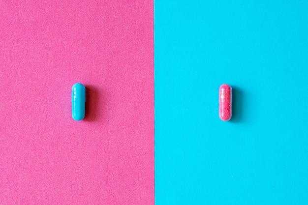 Capsules roses et bleues, pilules isolées sur fond rose et bleu