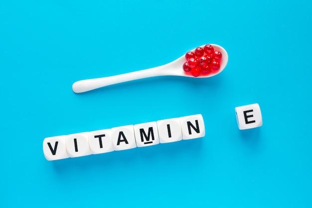 Capsules rouges dans la cuillère blanche vitamine e