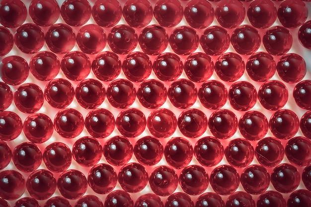 Capsules rouges sur un gros plan de fond blanc.