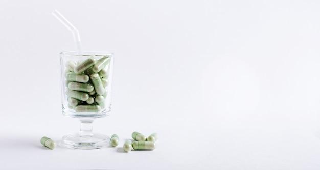 Capsules vertes dans un verre à cocktail sur une surface blanche