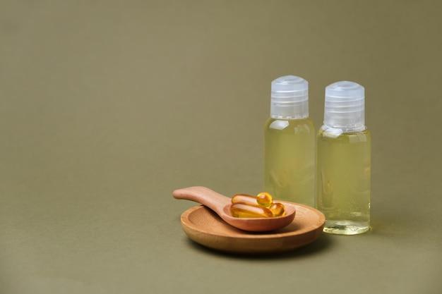 Capsules avec des vitamines dans la cuillère en bois sur la surface verte, et bouteilles d'extrait