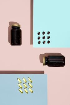 Capsules de vitamines pilules de lécithine et pilule oméga dans une bouteille en verre sur fond rose et bleu à la mode