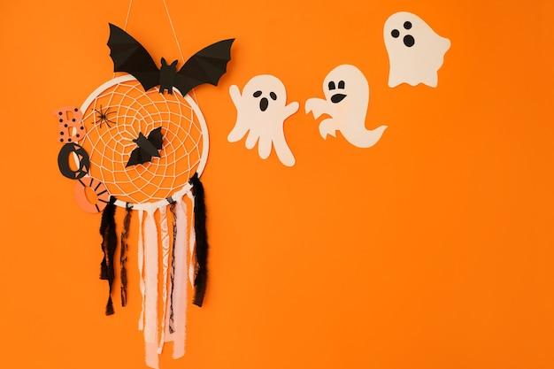Un capteur de rêves avec des araignées et une chauve-souris sur fond orange avec des fantômes est un concept d'halloween