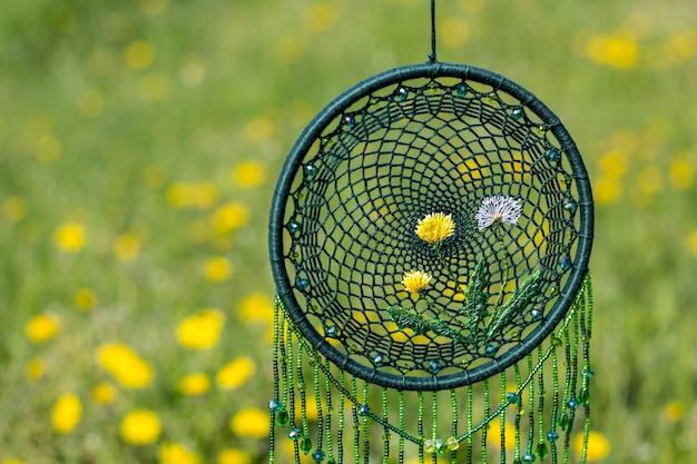 Capteur de rêves fait main dans un champ fleuri