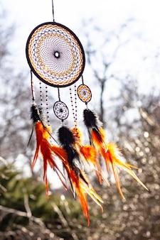 Capteur de rêves avec fils de plumes et corde de perles suspendus.