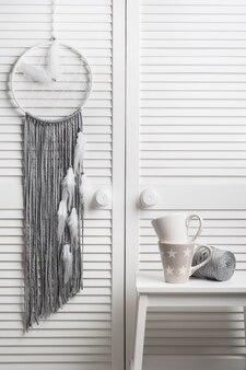 Capteur de rêves gris avec des plumes blanches
